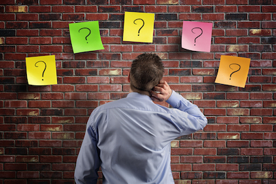 man looking at stickie notes of question marks on the wall. Overwhelmed by the options.