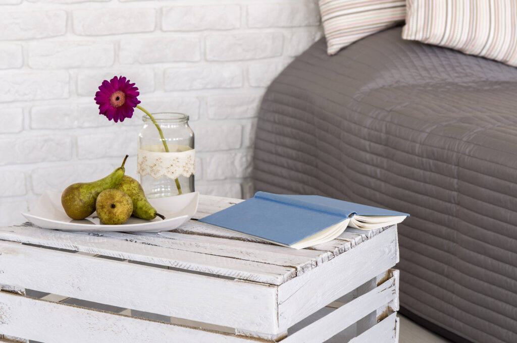 go to bed bedside table with book and flower.